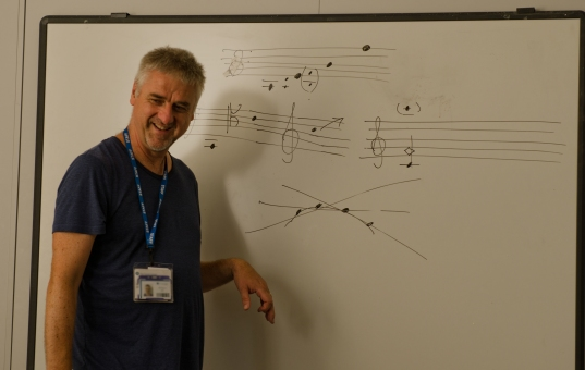 Man laughing with whiteboard with score behind