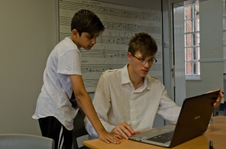 Composer teaching young composer with a laptop