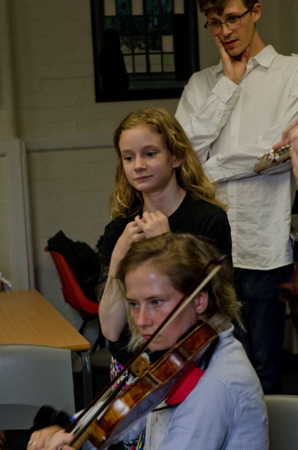 Young composer watching violinist performing her piece