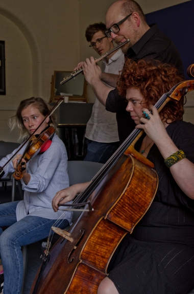 Violinist, cellist and flautist with assistant composer performing