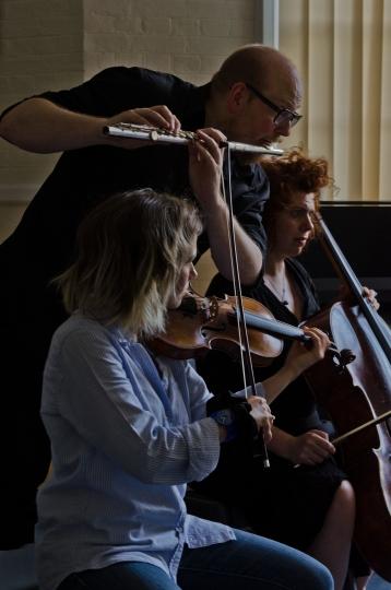Flautist, Violinist and Cellist performing