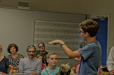 A young composer tells a crowd about his piece