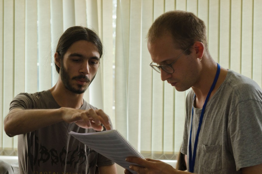 A young composer and a tutor looking at a score