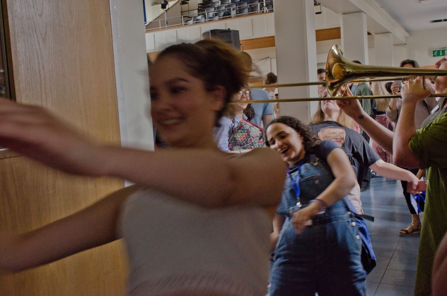 Young people leaving a hall limboing under a trombone