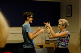 Young composer and woman pointing at one another, they are both smiling