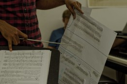 a close up of a conductor holding manuscript paper