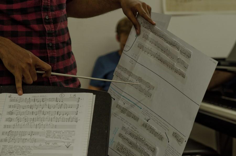 a close up of a conductor holding manuscript paper