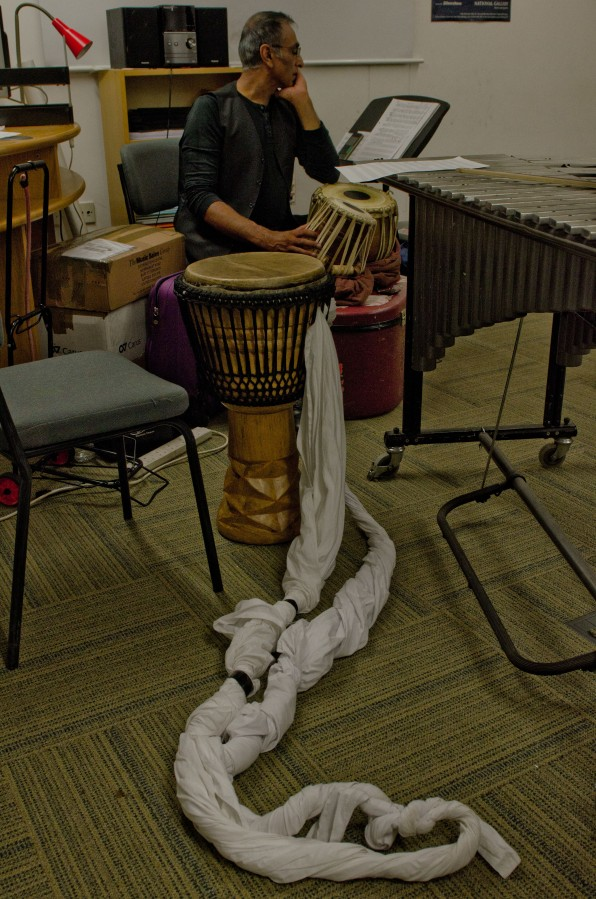 a percussionist sitting and looking at a score
