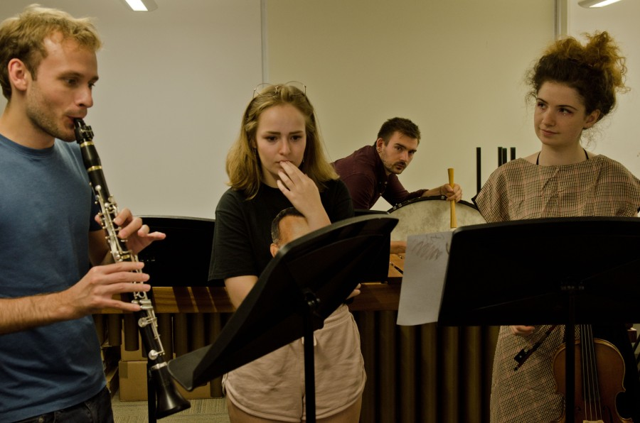 A young composer watching as musicians perform their work