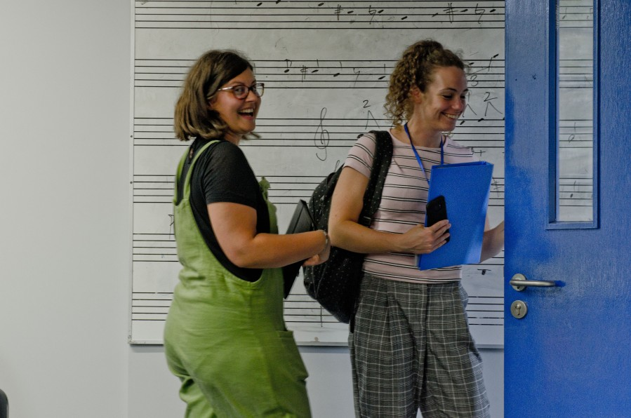 Two women leaving a room smiling, music is on the board behind them