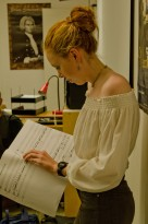 A young female composer holding a score and looking at it