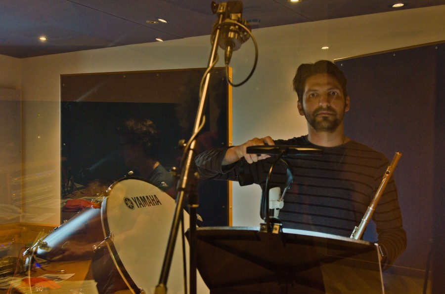 a performer setting up in a recording studio, taken through glass