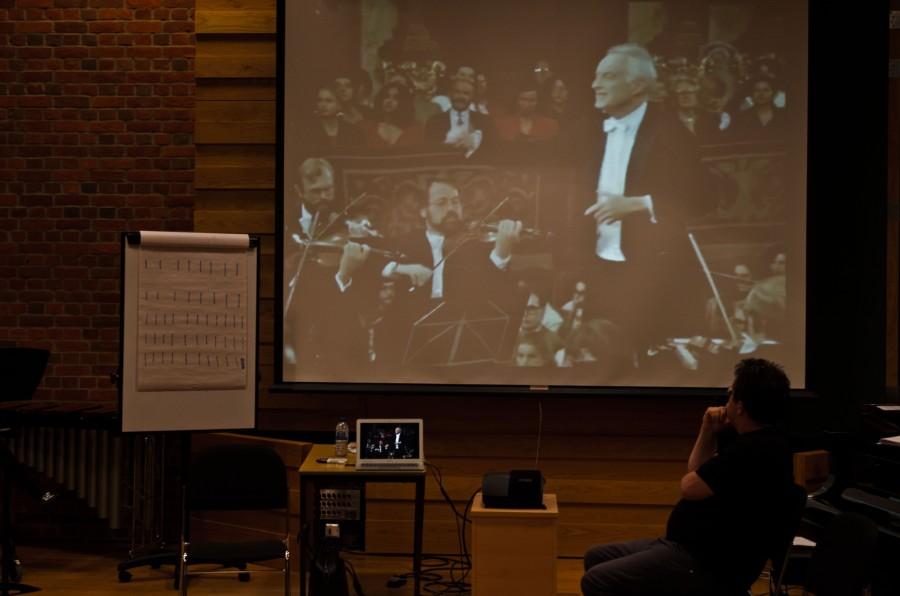 A man watches a video of Leonard Bernstein conduction