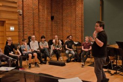 A man addresses a group of young composers