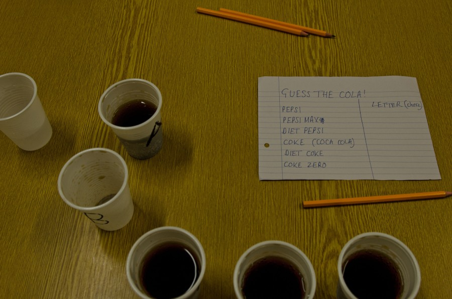 """Different drinks laid out with a piece of paper saying """"guess the cola"""""""