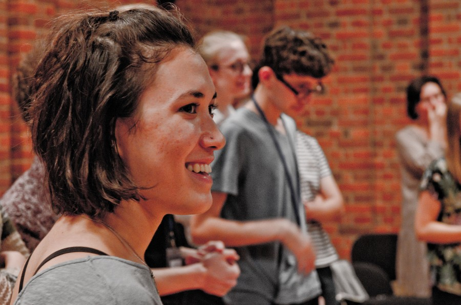 a young female composer smiling, other people are out of focus in the background