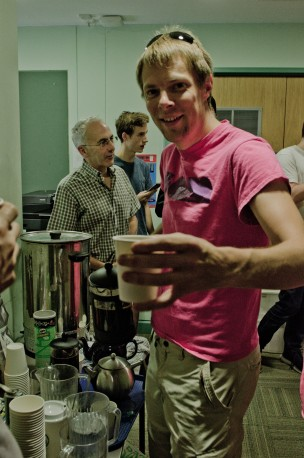 A man offers a cup of coffee to the camera, people are milling about in the background