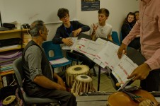 A Tabla player discusses a score with young composers
