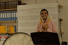 A young man holding drum sticks and smiling, music is written on a whiteboard behind him