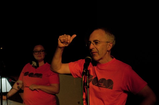 A man in an orange t-shirt talks into a microphone