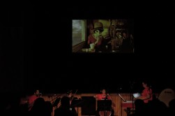 Musicians perform in front of a projected film