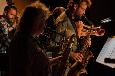 Saxophonists playing in spotlights, photo from the side