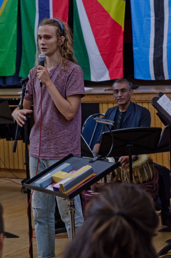 A young composer explains his work, holding a microphone