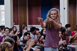 A young composer in a burgundy t-shirt pointing at someone out of shot
