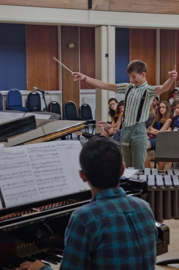 A young composer in a green and white striped shirt conducts