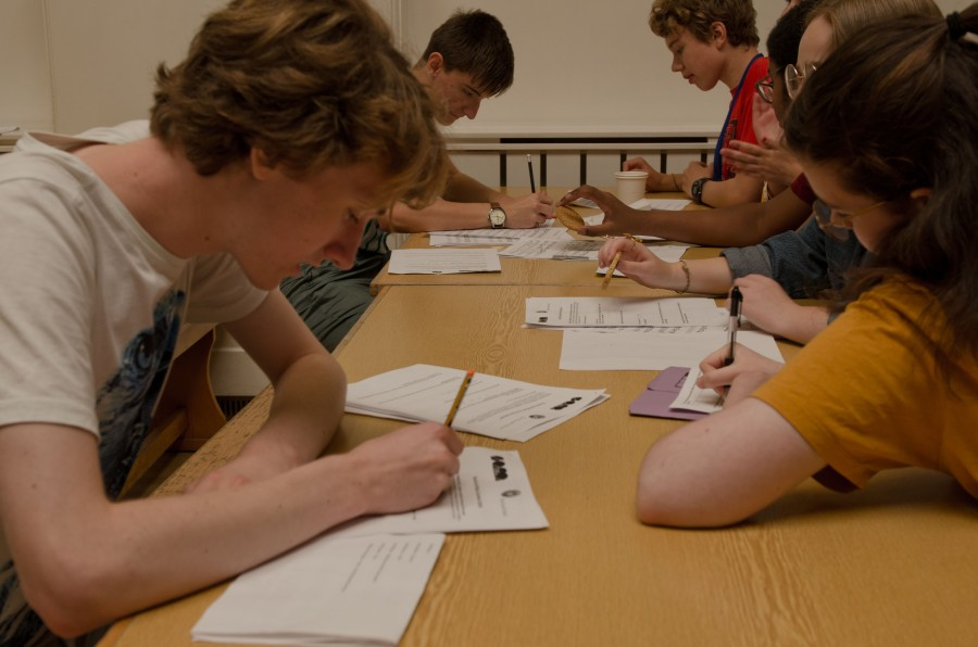 Young composers filling out forms on a table