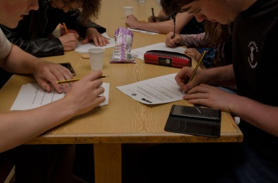 Young composers filling out forms on a table (close up of hands)