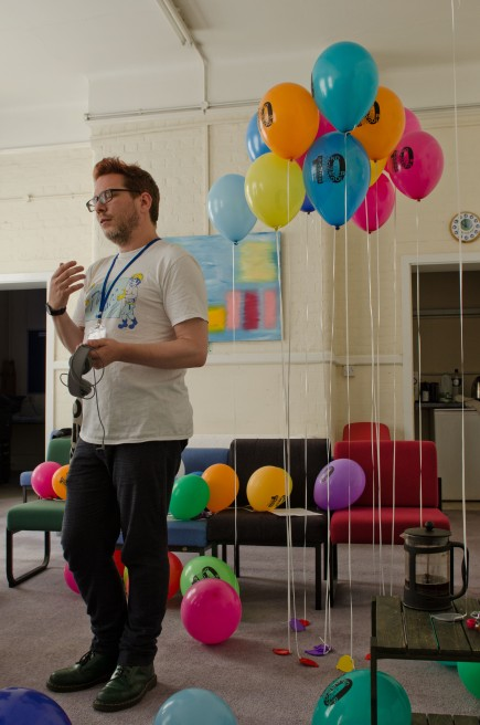 A man gesticulating with many multicoloured balloons next to him
