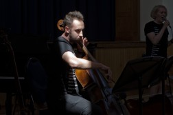 A Cellist, lit by a shaft of light, performs