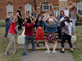 A group of young composers and tutors dancing and smiling on steps