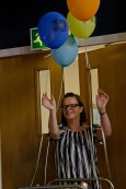 Victoria Johnson a woman in a stiped top enters a doorway with cake and balloons