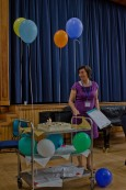 A woman, Judith Robinson, Looking at a trolley with Cake and Balloons